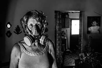 "11-18-2014, Libero, Province of Entre Ríos. Marta Elsa Cian (1947). Poultry farmer. In town, they call her ""the masked crazy woman"" because every time she leaves her home she has to wear a protective mask to avoid inhaling the continuous drifts of agrotoxins sprayed in the vicinity of her house.  In 2001, she suffered exposure to multiple agrochemicals employed in soybean and rice monoculture crop farming which affected her health causing chronic respiratory failure, hypertension, neuropathies combined with hematological and cardiologic symptoms.   11-18-2014, Libero, Province of Entre Ríos. Marta Elsa Cian (1947). Poultry farmer. In town, they call her ""the masked crazy woman"" because every time she leaves her home she has to wear a protective mask to avoid inhaling the continuous drifts of agrotoxins sprayed in the vicinity of her house. In 2001, she suffered exposure to multiple agrochemicals employed in soybean and rice monoculture crop farming which affected her health causing chronic respiratory failure, hypertension, neuropathies combined with hematological and cardiologic symptoms."