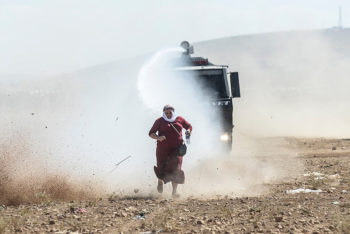A Kurdish woman runs away from a water cannon near the Syrian border after Turkish authorities temporarily closed the border at the southeastern town of Suruc in Sanliurfa province, on September 22, 2014. Tens of thousands of Syrian Kurds flooded into Turkey on Saturday, fleeing an onslaught by the jihadist Islamic State group that prompted an appeal for international intervention. AFP PHOTO/BULENT KILIC