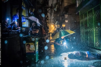 MANILA, PHILIPPINES - OCTOBER 11: Heavy rain pours as SOCO Police, Scene of the Crime Operatives, investigate inside an alley where victim, Romeo Joel Torres Fontanilla, 37, was killed by 2 unidentified gunmen riding motorcycles early Tuesday morning on October 11, 2016 in Manila, Philippines.  Photo by Daniel Berehulak for The New York Times